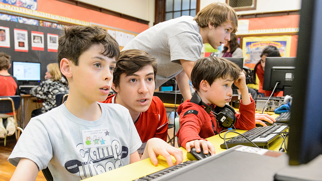 UW students George Kunesh (left) and James Plautz (right) work with students enrolled in a UW-Madison Computer Science Catapult Club at Randall Elementary School