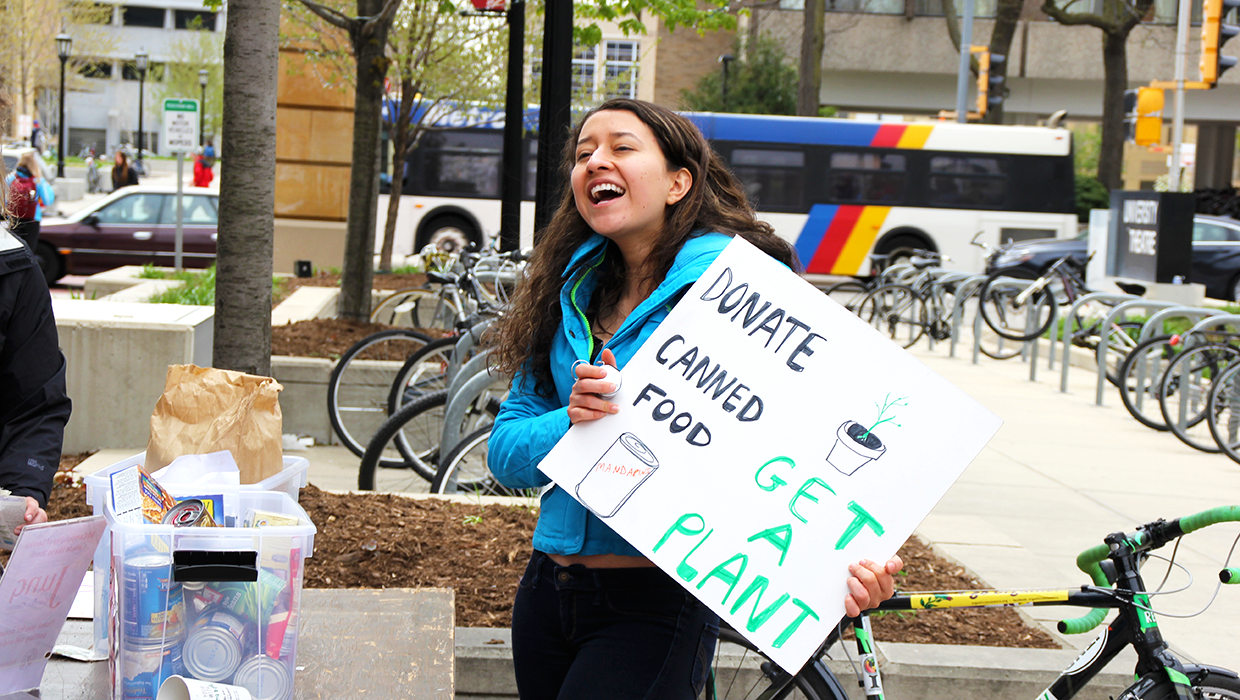 A student holds a sign asking students to donate food at the 2016 All Campus Day of Service
