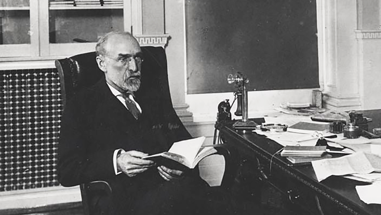 Charles Van Hise reading at his desk